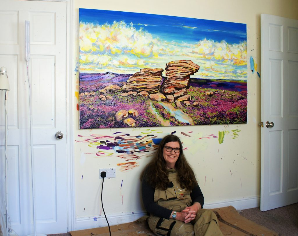 Donna Brewins-Cook in front of her painting High Summer Ox Stone